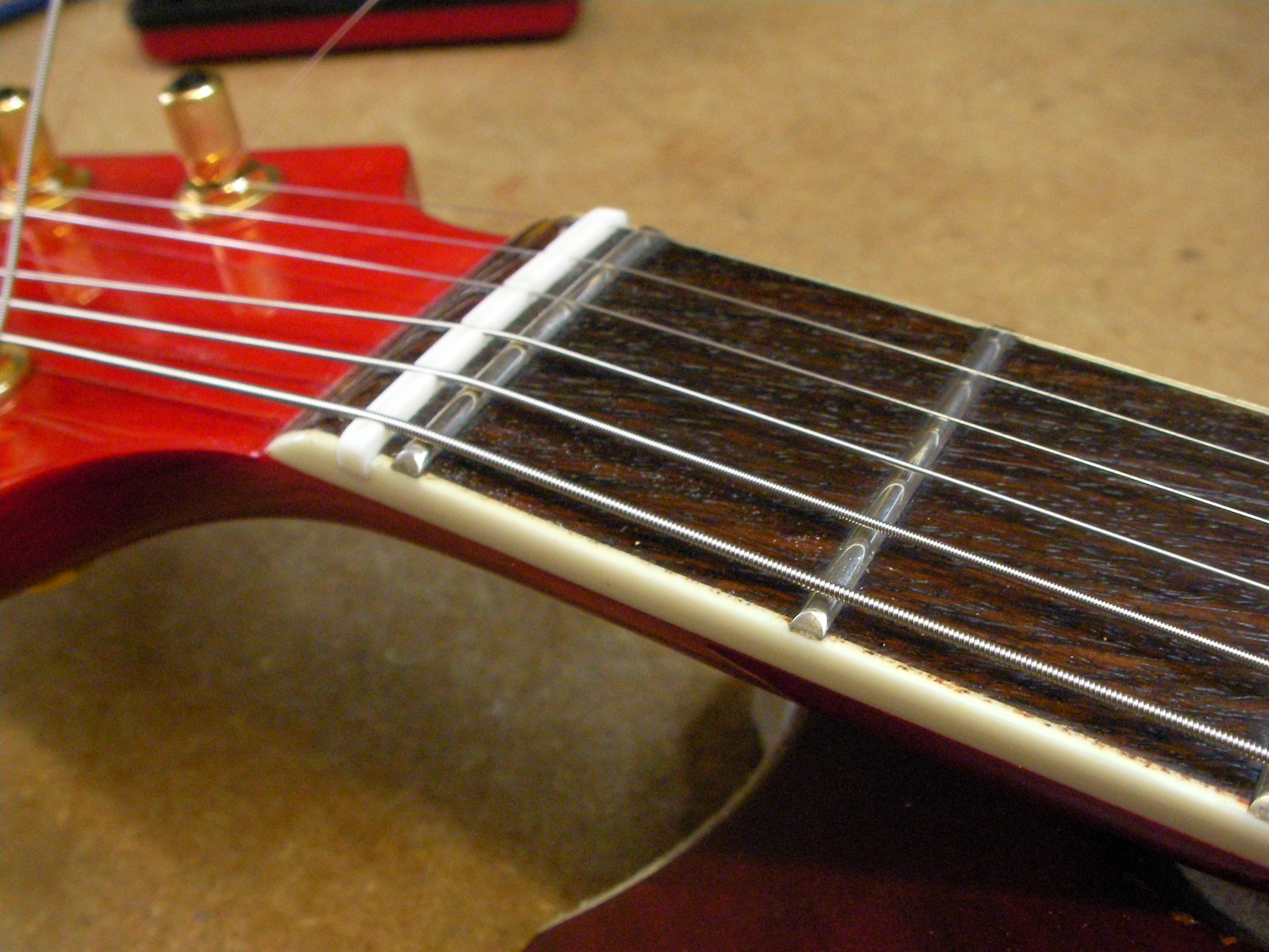how to change the action on a guitar
