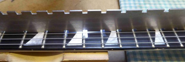 Assessing the neck curvature of a Jackson Guitar with a calibrated straight edge.