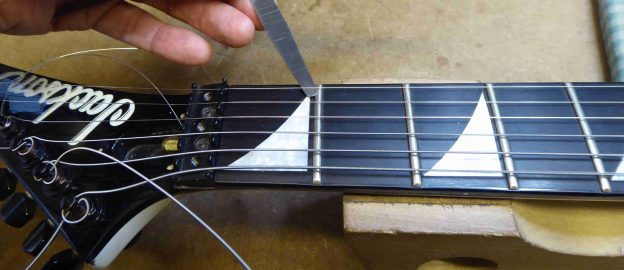 Using a feeler gauge to check the action height at the first fret on a Jackson Guitar
