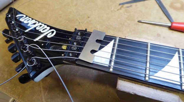 A shim which will be placed under the locking nut of a Jackson guitar in order to raise the action at the first fret.