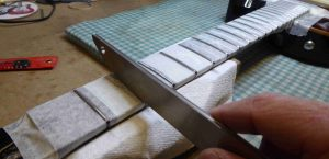 Rounding off the fret tops with a fret crowning file.