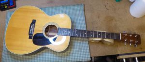 Martin acoustic guitar on the bench prior to the new bone nut and saddle being fitted