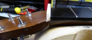 A bone nut blank fitted into the slot on a Martin acoustic. the bottom now angled to fir properly