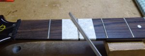 Filing down the top of a hight fret on a Gibson Firebird