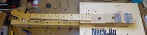 A fender Stratocaster neck bolted on to a Stew MacDonanld neck jig