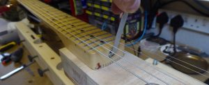 Adjusting the truss rod on the heel of a Stratocaster neck whilst bolted on to a Stew Macdonald neck jig